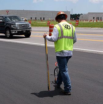 A worker taking measurements on freshly laid asphalt
