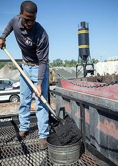 An employee shoveling manufactured asphalt
