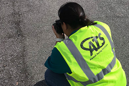 A worker photographing asphalt damage