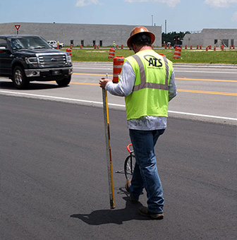 A worker taking measurements on freshly laid asphalt