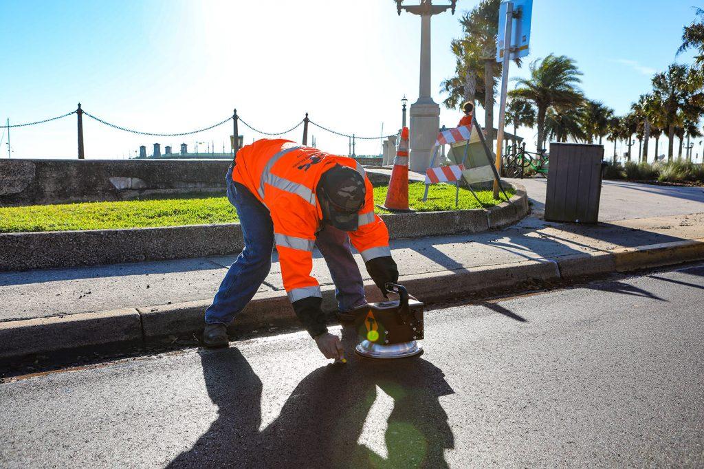 Asphalt Testing Solutions & Engineering Roadway Specialist checks density gauge.