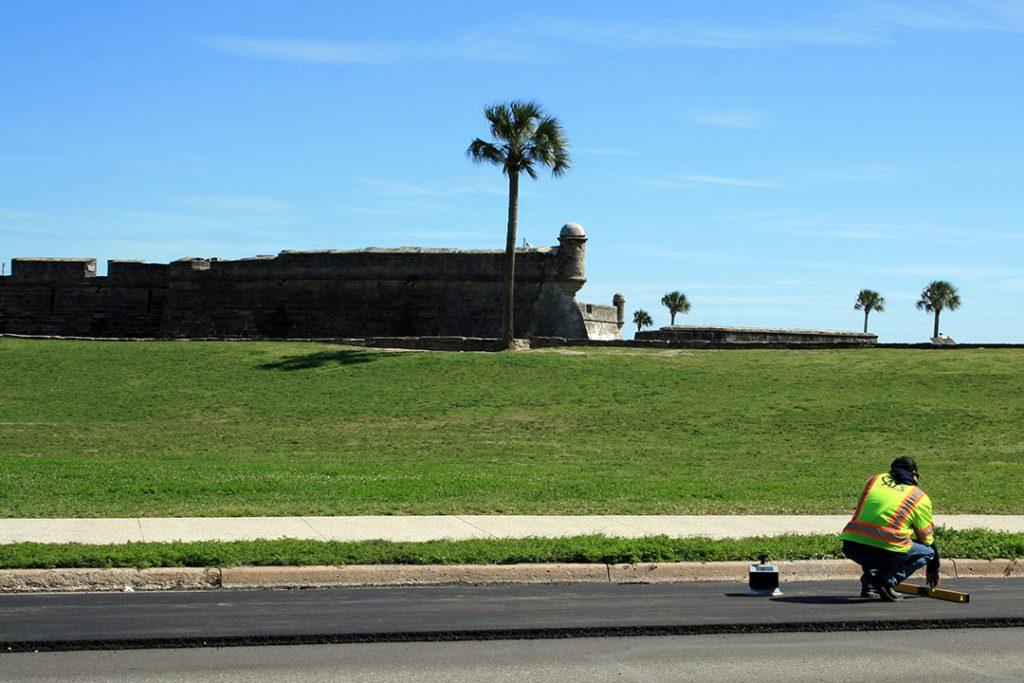Asphalt Testing Solutions & Engineering Roadway Specialist uses straightedge in front of St. Augustine's Castillo de San Marcos